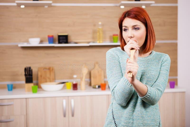 Zeer het gelukkige roodharigevrouw zingen in de keuken royalty-vrije stock foto