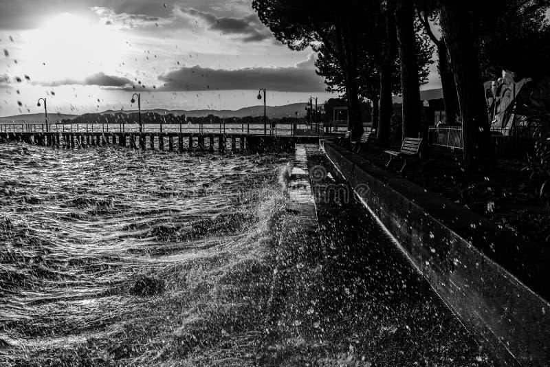 Zeer hoogwatergolven die op een meerkust bespatten, met dalingencomi stock afbeelding