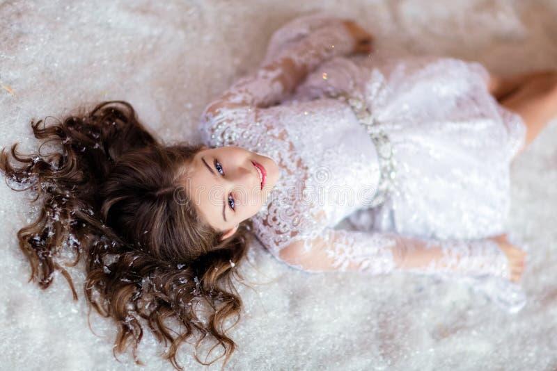 Zeer leuk krullend jong meisje die en op de vloer in glimlachen liggen royalty-vrije stock afbeeldingen