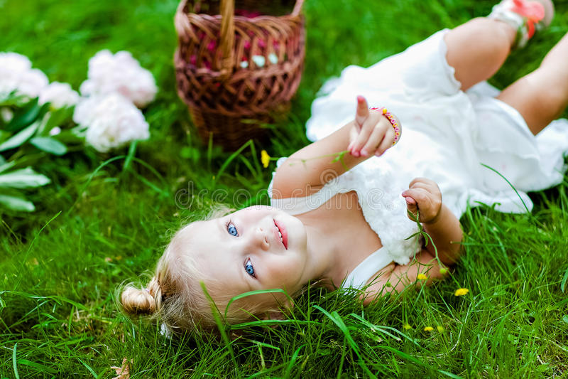 Zeer leuk weinig blondemeisje in een witte kleding die op het gras liggen royalty-vrije stock foto