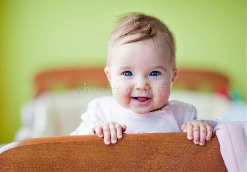 Zeer leuke babyglimlachen die zich in de voederbak bevinden stock afbeelding