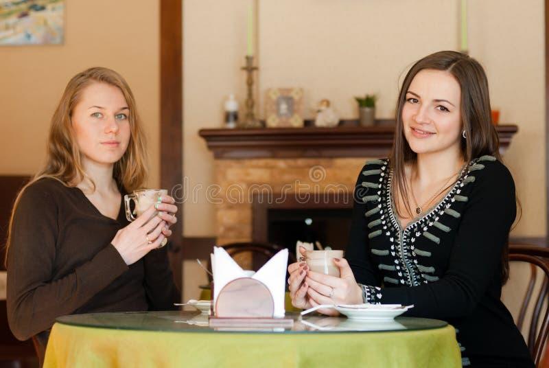 Mooie glimlachende meisjes die koffiezitting binnen in koffiebistro drinken royalty-vrije stock foto