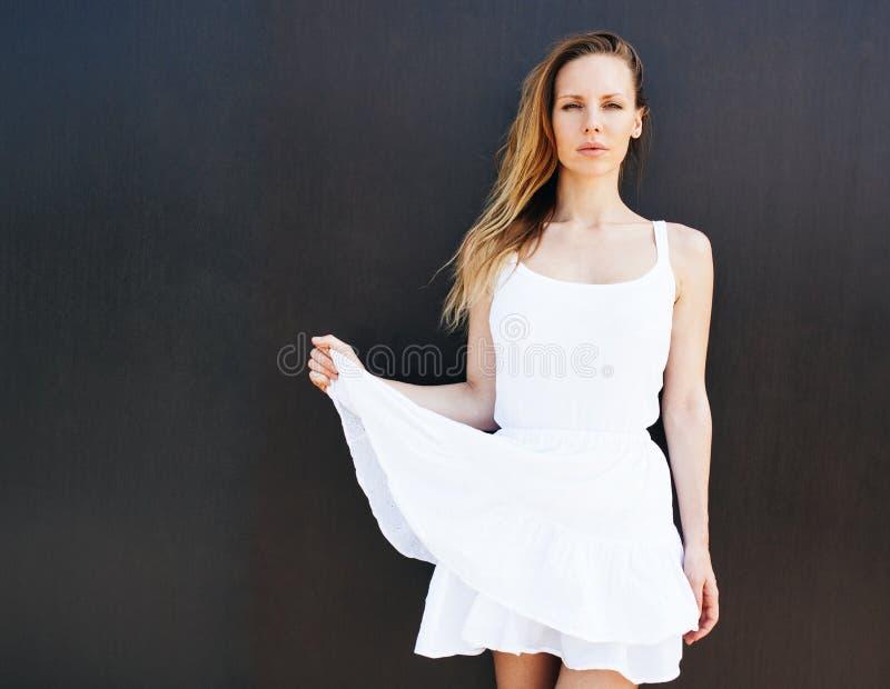 Zeer mooi blondemeisje in het korte witte kleding stellen op de straat dichtbij een zwarte muur Zonnige dag De wind blaast haar h royalty-vrije stock afbeeldingen