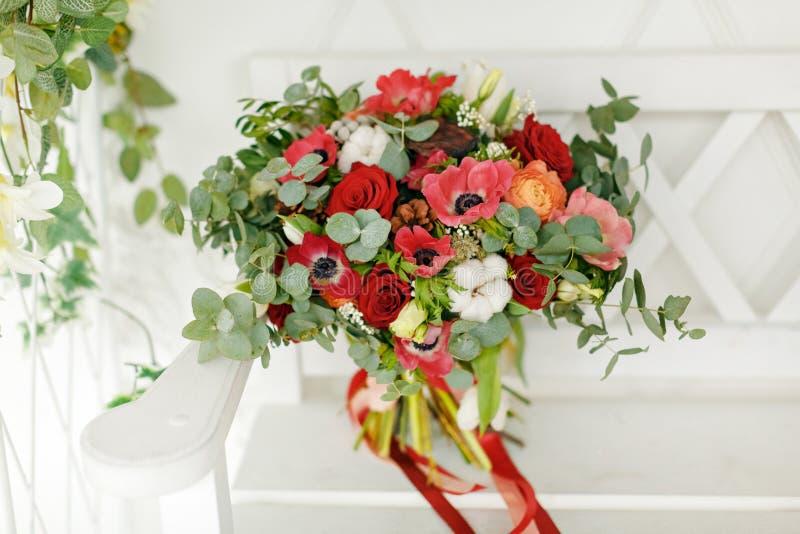 Zeer mooi helder bruids boeket met rode bloemen, tribunes op een witte bank royalty-vrije stock fotografie
