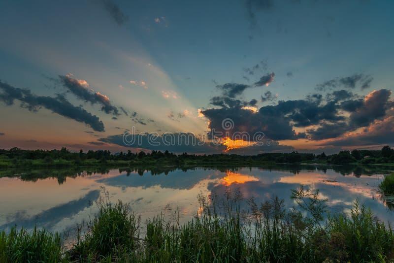 Zeer mooie de zomerzonsondergang over het meer met bezinning over water royalty-vrije stock afbeeldingen