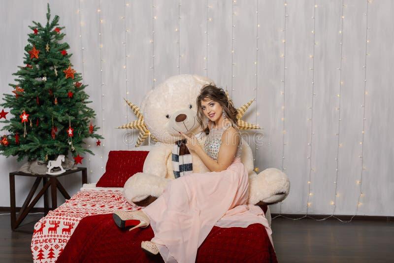 Zeer mooie en sexy vrouw in een roze kleding met een grote beer in het decor van het Nieuwjaar, die in de stijl van het Nieuwjaar royalty-vrije stock afbeelding