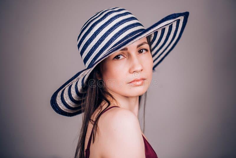 Zeer mooie leuke vrouw die in gestreepte hoed op grijze achtergrond camera bekijken royalty-vrije stock afbeelding