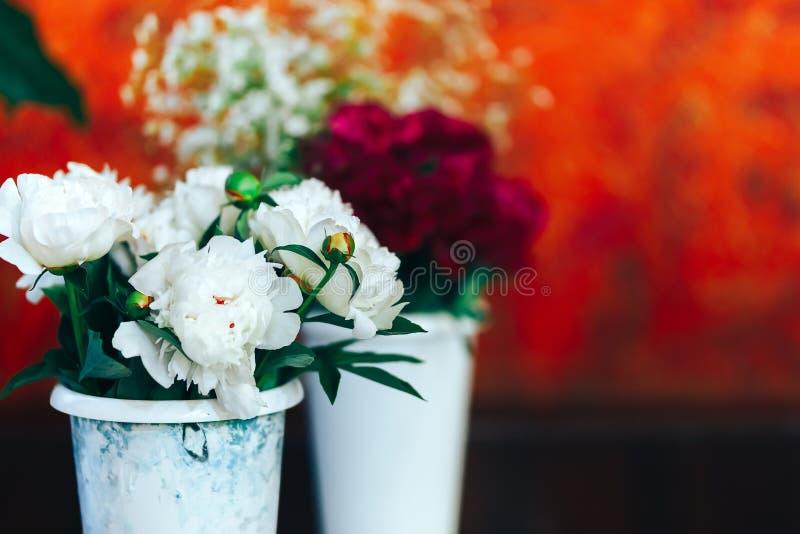 Zeer mooie pionen in vazen die zich op lijst, gift voor vrouw bevinden stock afbeelding