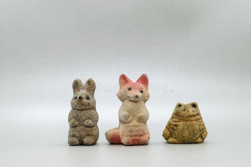 Zeer oud konijntje, vos en kikker zacht speelgoed op grijze oppervlakte als achtergrond stock fotografie