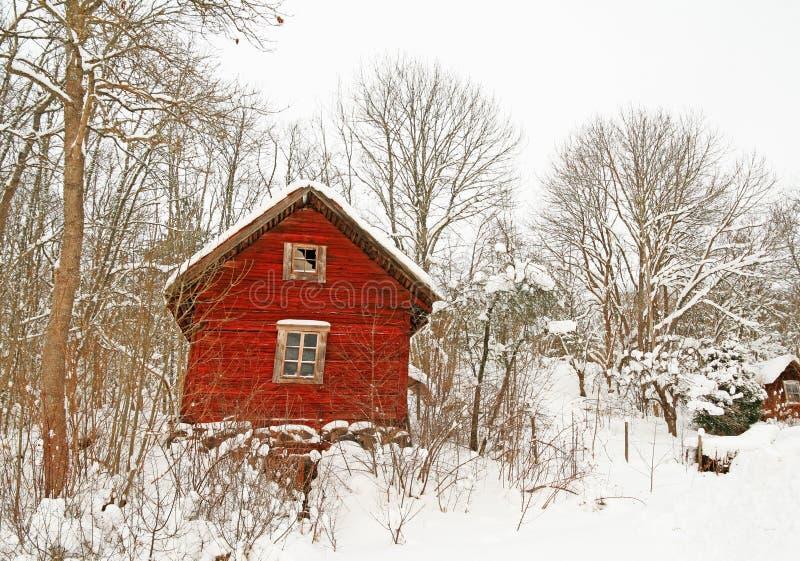 Zeer oud rood blokhuis in een sneeuwbos royalty-vrije stock fotografie
