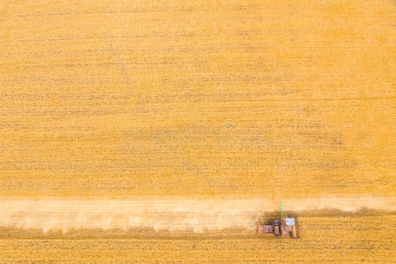 Zeer oud Ruw Combine oogst tarwe in het veld bij zonsondergang in de herfst in Rusland weergave vanaf hoogte stock afbeelding