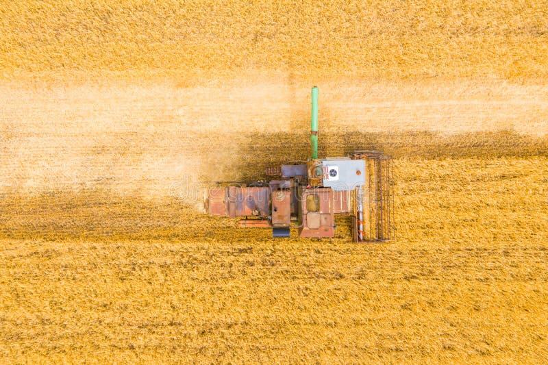 Zeer oud Ruw Combine oogst tarwe in het veld bij zonsondergang in de herfst in Rusland weergave vanaf hoogte royalty-vrije stock fotografie