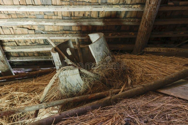 Zeer oude en gebroken houten ton die in de schuurzolder liggen op hooistro stock foto's