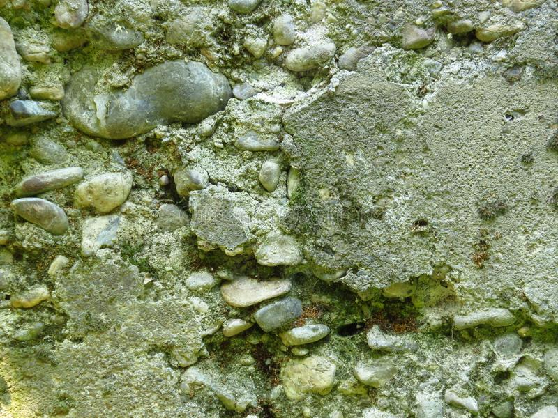 Zeer oude geruïneerde cement concrete muur Gebarsten die metselwerk met mos wordt behandeld stock fotografie
