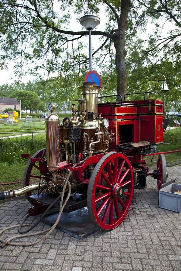 Zeer oude rode brandmotor op straat stock foto