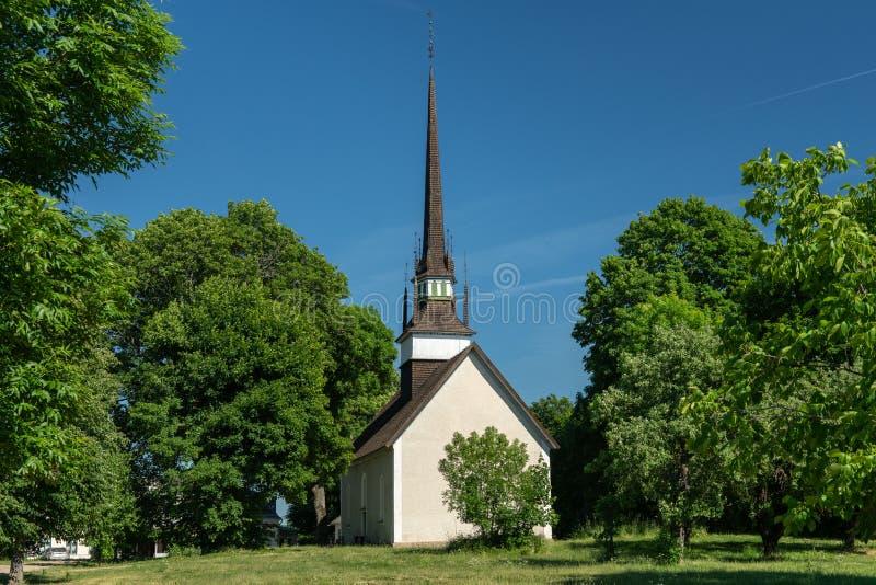 Zeer oude witte kerk met lange en smalle toren royalty-vrije stock foto's