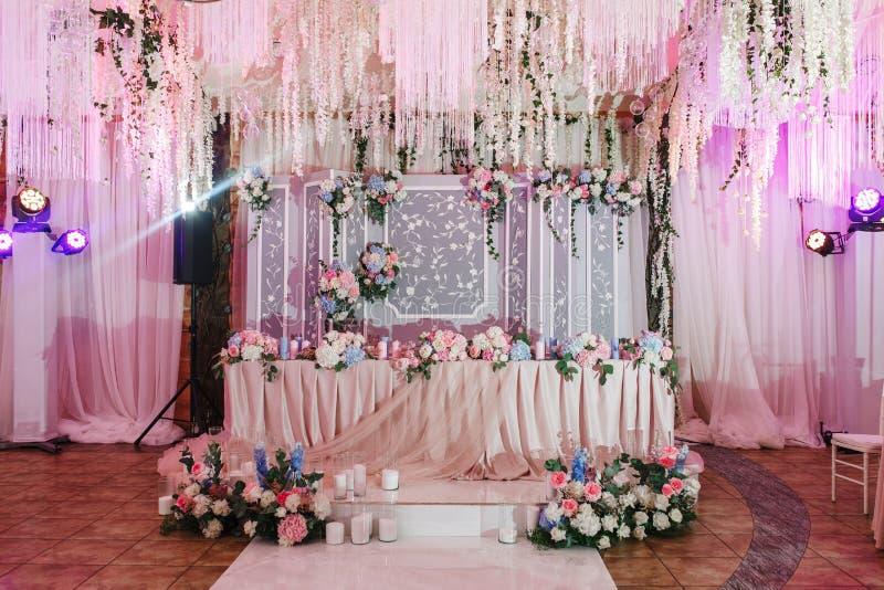 Zeer prachtig verfraaide restaurantzaal voor huwelijksviering Natuurlijke roze bloemen royalty-vrije stock afbeeldingen