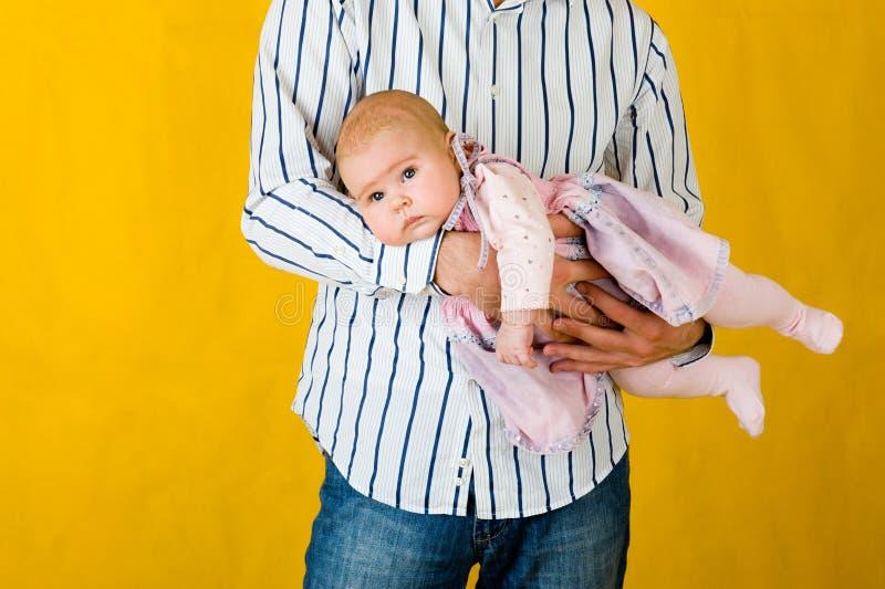Zeer vermakelijk kind bij vaderhanden. royalty-vrije stock foto's