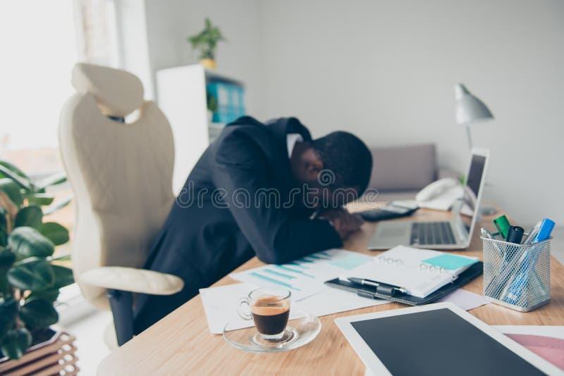 Zeer vermoeide mens met zwarte huideconoom, slaap op zijn handenwhi royalty-vrije stock foto's