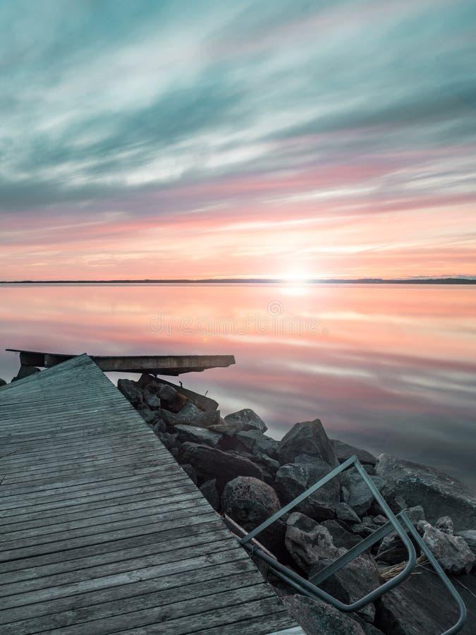 Zeer weerspiegelende zonsondergang over meer in Zweden stock afbeeldingen