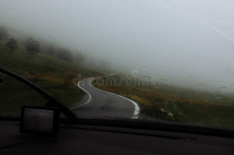 Zeer zware regen met mist of wolken, slechte hamel, Regendruppels bij autoraam stock fotografie