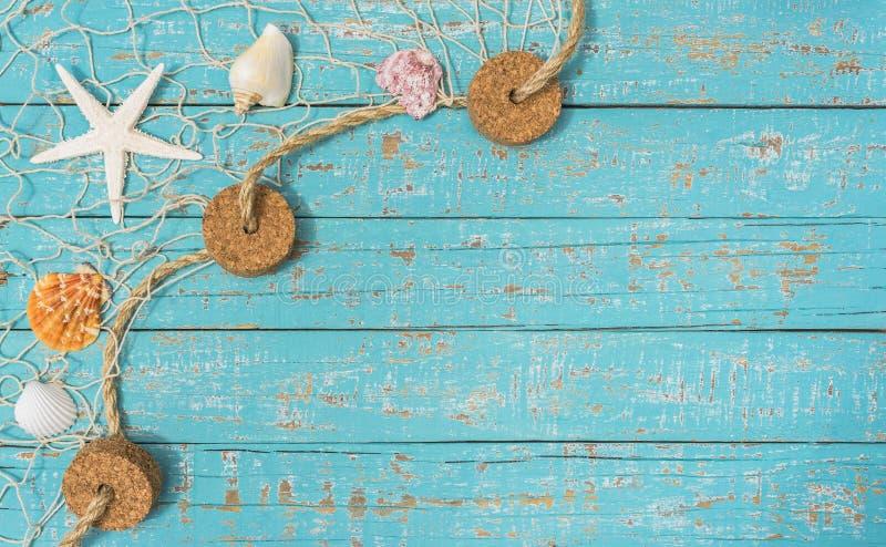 Zeeschelpen en overzeese ster in visnet op lichtblauwe rustieke houten achtergrond royalty-vrije stock afbeelding