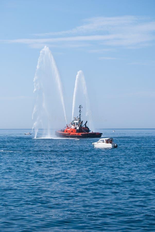Zeeschip van brandbestrijders met hoge plonsen van zeewater stock afbeeldingen