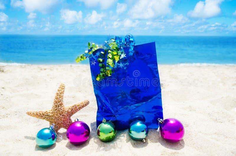 Zeester met Kerstmisballen en giftzak op het strand royalty-vrije stock afbeelding