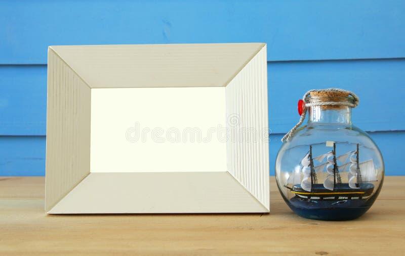 Zeevaartconcept met lege fotokader en zeilboot in de fles over houten lijst Voor fotografiemontering stock afbeeldingen