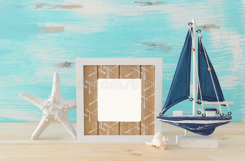Zeevaartconcept met lege fotokader en zeilboot over houten lijst Voor fotografiemontering stock afbeelding