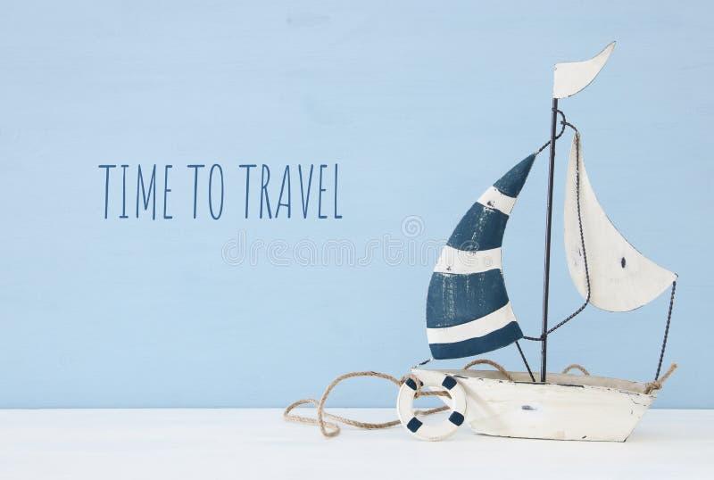 zeevaartconcept met zeilboot over witte houten lijst en teksten: tijd te reizen royalty-vrije stock afbeelding