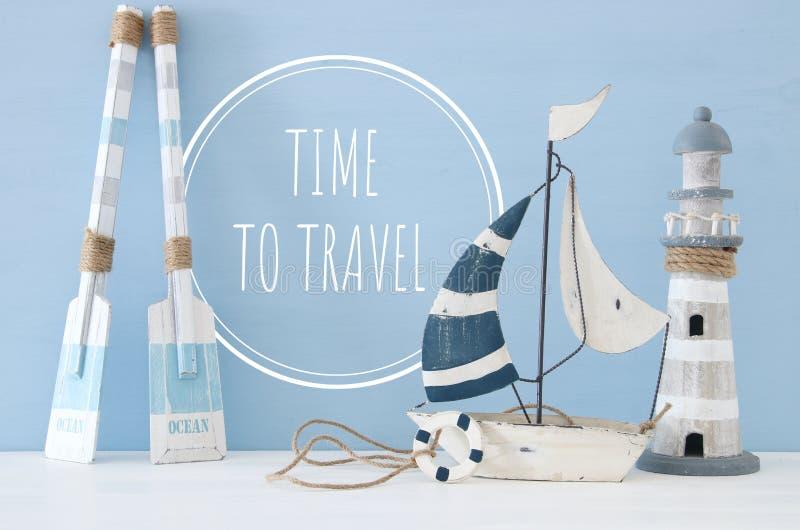 zeevaartconceptenbeeld met decoratieve roeispanen, boot en vuurtoren over lichtblauwe achtergrond stock afbeeldingen