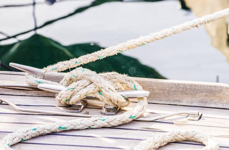 Zeevaartknoop, cleat en kabel op houten dek van varend jacht stock fotografie