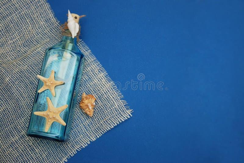 Zeevaartthemaachtergrond, Decoratieve Fles met Shells, Zeester op de blauwe Achtergrond van Depp De ruimte van het exemplaar Sele royalty-vrije stock fotografie