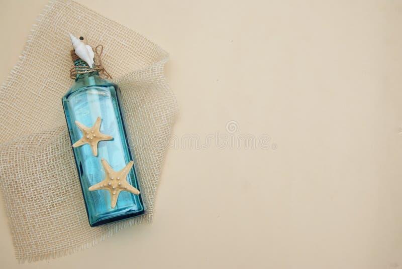 Zeevaartthemaachtergrond, Decoratieve Fles met Shells, Zeester op Neutrale Ivoorachtergrond Plaats voor tekst Selectieve nadruk royalty-vrije stock fotografie
