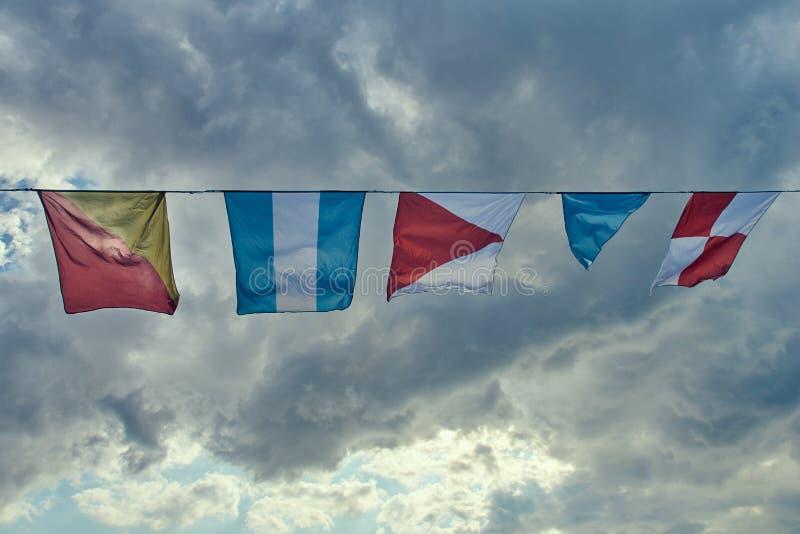 Zeevlaggen die in de wind tegen de hemel fladderen royalty-vrije stock afbeelding