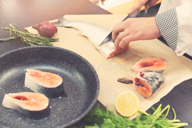 Zeevruchten - chef-kok het snijden zalmvissen voor het voorbereidingen treffen stock fotografie
