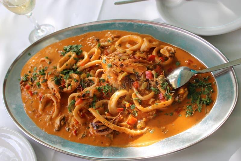 Zeevruchten in een rode saus stock afbeeldingen