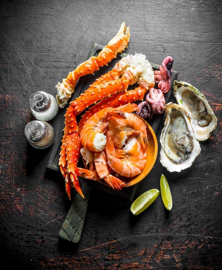 Zeevruchten Krab, garnalen, oesters, babyoctopus op een knipselraad met kruiden en kalkplakken royalty-vrije stock foto's