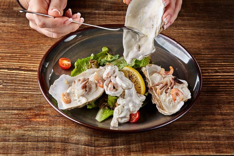 Zeevruchten Restaurantkeuken, gezond delicatessenvoedsel Oesters, garnalen, octopus in witte roomsaus in shell van royalty-vrije stock afbeelding