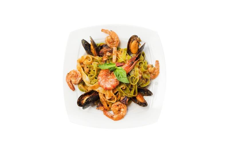 Zeevruchtendeegwaren met mosselen, garnalen, tomatensaus, basilicum, parmezaanse kaas cheeseon witte plaat Spaghetti die op witte royalty-vrije stock foto