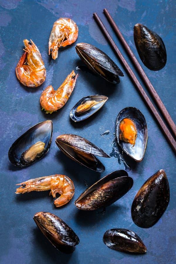 Zeevruchtenmosselen in shell en garnalen op een blauwe achtergrond stock afbeeldingen