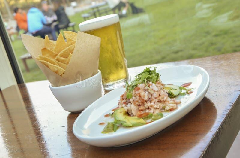 Zeevruchtensalade met spaanders en bier stock foto's