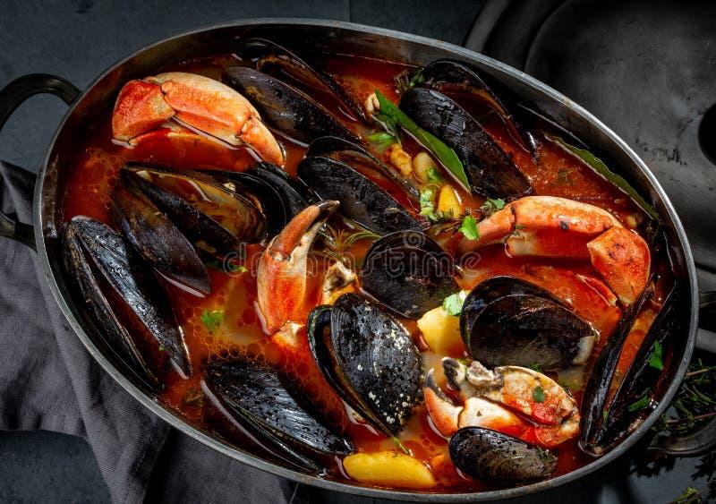 Zeevruchtensoep met mosselen en krabben in metaalpot stock foto