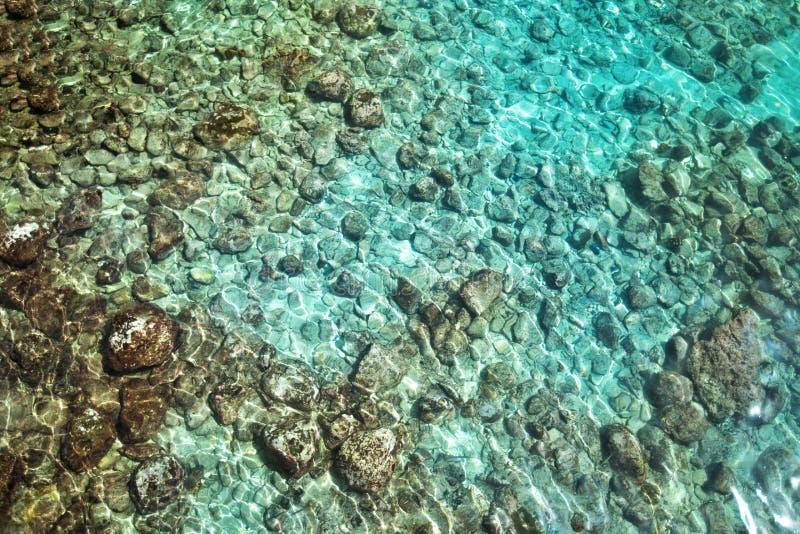 Zeewater met zonlicht op turkooise kiezelstenen stock foto's