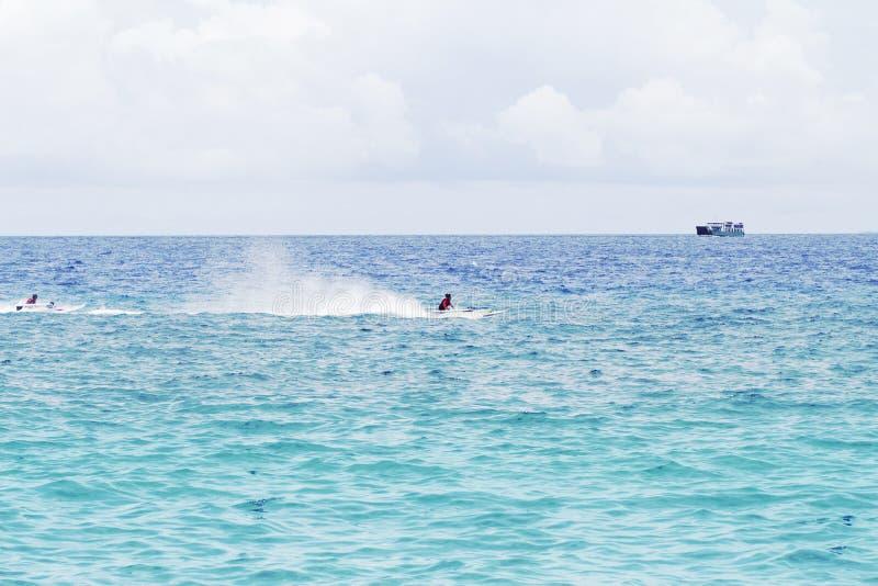 Zeewaterlandschap met vrachtschip op horizon en motorboot royalty-vrije stock foto's