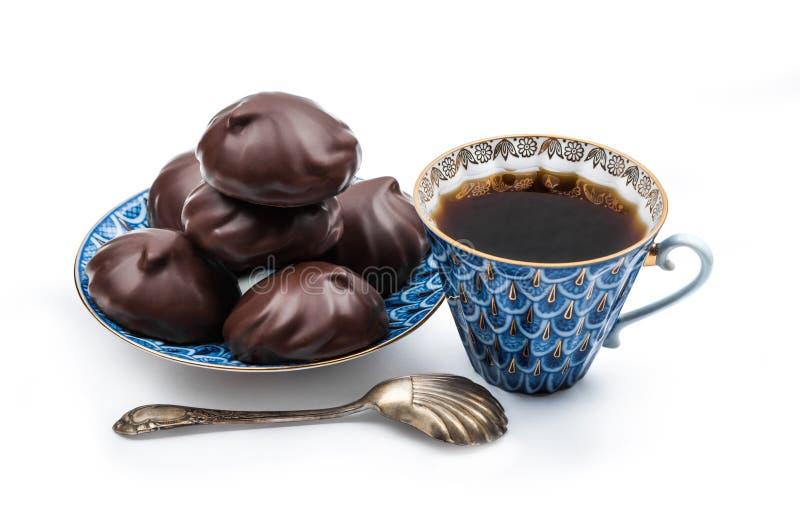 Zefir ricoperto di cioccolato russo su un piattino blu e su un coffe nero fotografie stock libere da diritti