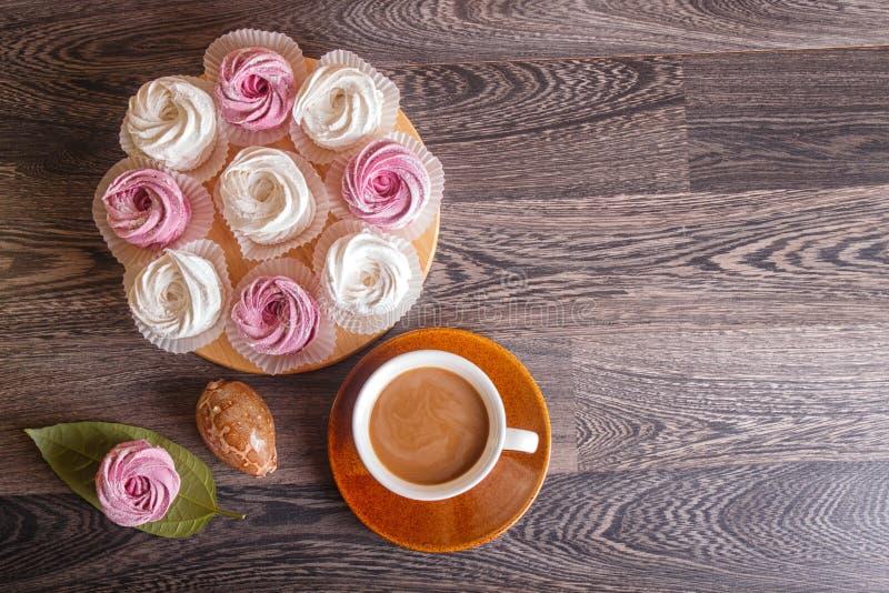 Zefiro rosa e bianco delle caramelle gommosa e molle con la tazza di caffè su un gra immagine stock