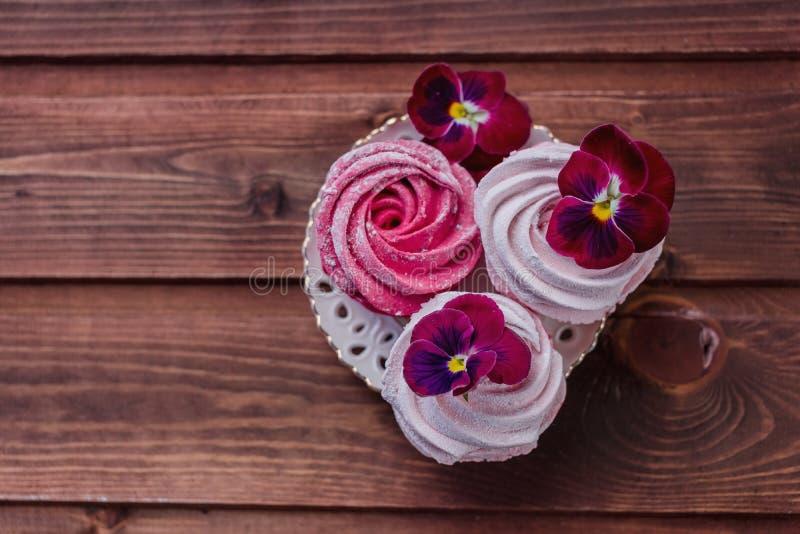 Zefiro variopinto e fiori su fondo di legno scuro Insieme dello zefiro casalingo o della caramella gommosa e molle bianco e rosa  fotografia stock libera da diritti
