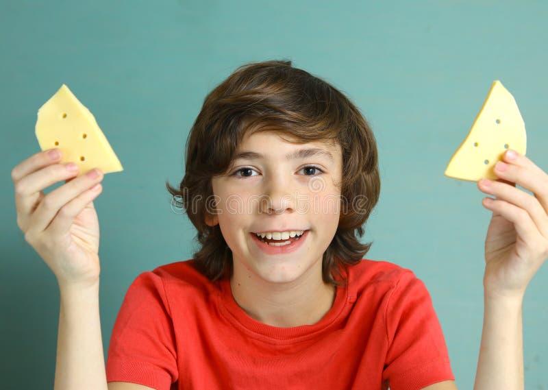 Zeg de kaasglimlach jongen met twee kaasplakken preteen stock fotografie
